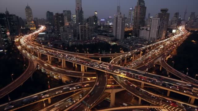 TL ZI Day to night traffic on elevated roads with the city in background. Shanghai, China