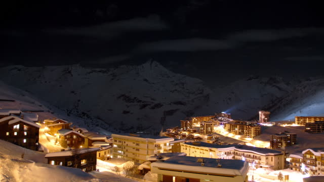 a day to night transition of a view across the high alp ski resort of tignes with snow covered mountain peaks in the distance - ウィンタースポーツ点の映像素材/bロール