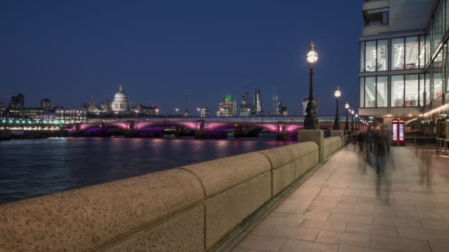 a day to night transition of people flowing along the thames embankment as the sun sets over london looking across the river thames towards blackfriars bridge st paul's and the financial district of the city of london - the end stock videos & royalty-free footage