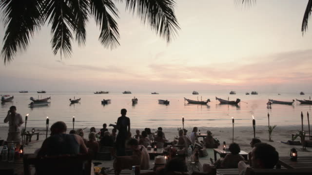TL, WS Day to night transition of tourists at a bar and on the beach at sunset / Koh Tao, Thailand