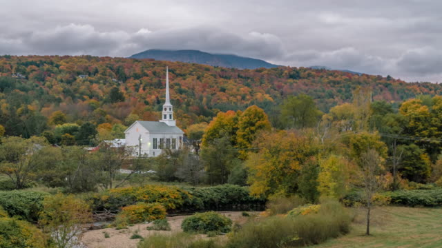 Day to night transition time lapse. Church in Stowe Vermont during autumn fall leaf peeping season.