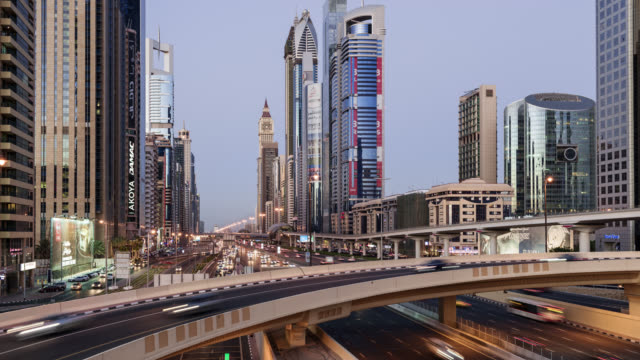 tl/ day to night transition time lapse of sheikh zayed road and dubai skyline, busy with commuting traffic at dusk, situated in dubai's financial district - light trail stock videos & royalty-free footage
