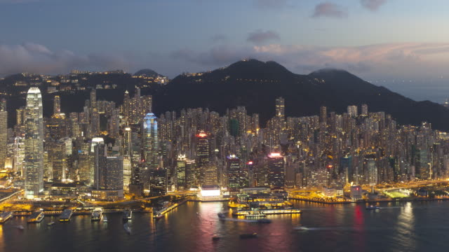 vídeos de stock, filmes e b-roll de  day to night transition, view over hong kong towards victoria peak, the illuminated skyline of central sits below the peak, hong kong, china, time-lapse - victoria peak