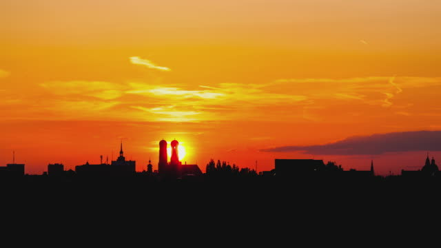 T/L day to night transition with the sun setting behind the famous 'Frauenkirche' - Munich's cathedral - as a silhoutte