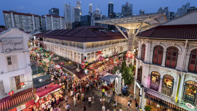 ws/tl/zi/pd day to night transition/ zoom in/pan down time lapse of chinatown during chinese new year, showing a busy night market and crowded streets set against the singapore skyline - nachtmarkt stock-videos und b-roll-filmmaterial