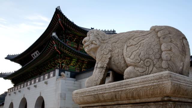 Day to night view of a Haetae (Mythical Unicorn-Lion) stone statue near Gwanghwamun gate in Jongno-gu