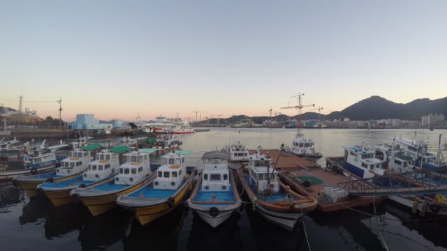 day to night view of anchored fishig boats at tongyeong dockyard - anchored stock videos & royalty-free footage