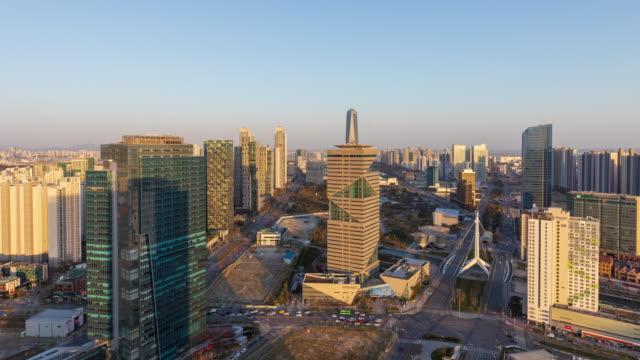 vídeos de stock e filmes b-roll de day to night view of g-tower and hosu 1 bridge in songdo international business district (songdo ibd) / yeonsu-gu, incheon, south korea - placa de nome de rua