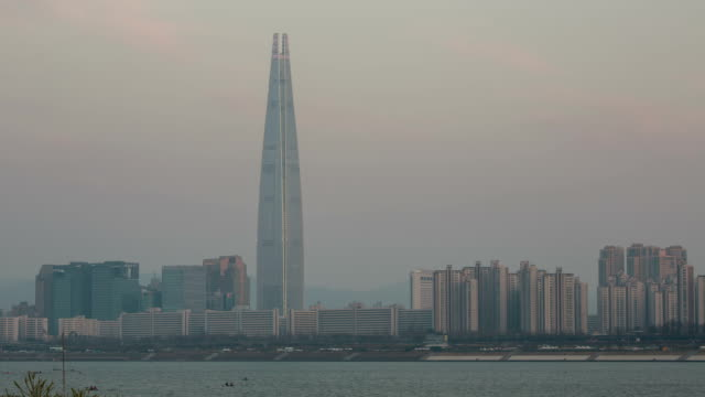 Day to night view of Lotte World Tower (one of the tallest building in Korea) covering with fine dust