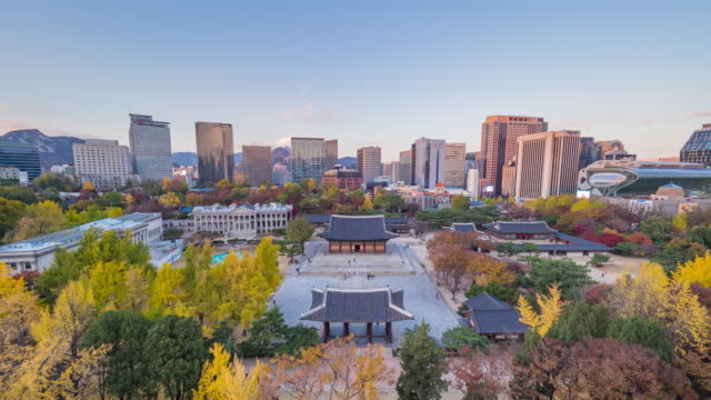 Day to night view of Seokjojeon Hall of Teoksugung Palace (One of the five Grand Palaces) with maple trees and surrounding Skyscrapers