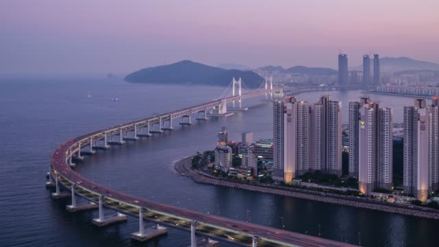 day to night view of the gwangan bridge(it is the longest bi-level bridge over the ocean in korea) on the sea and city buildings in haeundae, busan - complexity stock videos & royalty-free footage