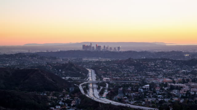 day to night view over a busy highway and los angeles skyline - elevated road stock videos & royalty-free footage