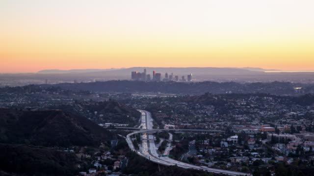 vídeos y material grabado en eventos de stock de day to night view over a busy highway and los angeles skyline - carretera elevada