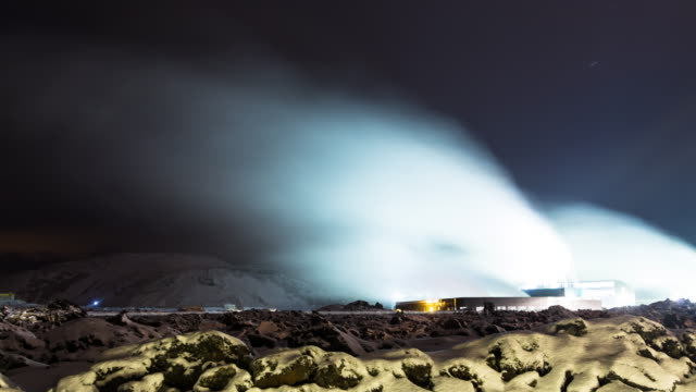 A day to night winter time lapse of the buildings surrounding the Blue Lagoon geothermal spa in Iceland featuring a mix of heavy, low, fast moving clouds overhead and thick steam rising from below