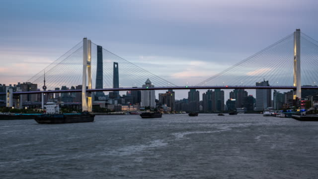 day to night zoom in time lapse of huangpu river under the nanpu bridge, shanghai, china - river huangpu stock videos & royalty-free footage