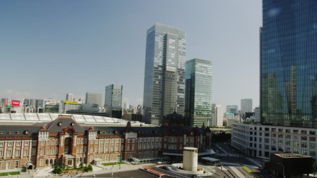 day view of tokyo station with office buildings surrounding it - marunouchi stock videos & royalty-free footage