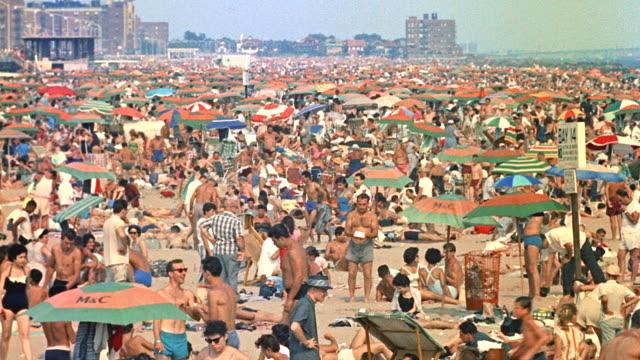 stockvideo's en b-roll-footage met day wide shot of crowded east coast beach; coney island (period 1958) - zonwering