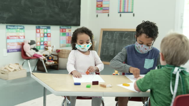 daycare students wearing masks while colouring - fatcamera stock videos & royalty-free footage