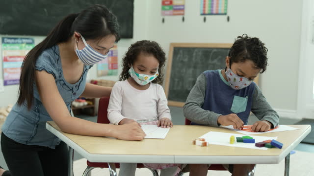 daycare students wearing masks while colouring - child care stock videos & royalty-free footage
