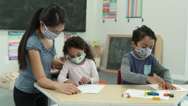 daycare students wearing masks while colouring - preschool child stock videos & royalty-free footage