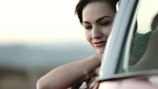 Daydreaming girl leans out of classic convertible and waves her hand in the wind