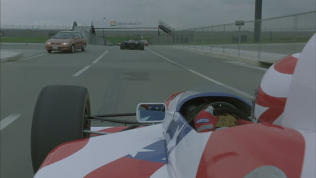 Daylight POV over left shoulder of formula one race car with American flag pattern following black race car swerving through oncoming traffic on three lane road or track.