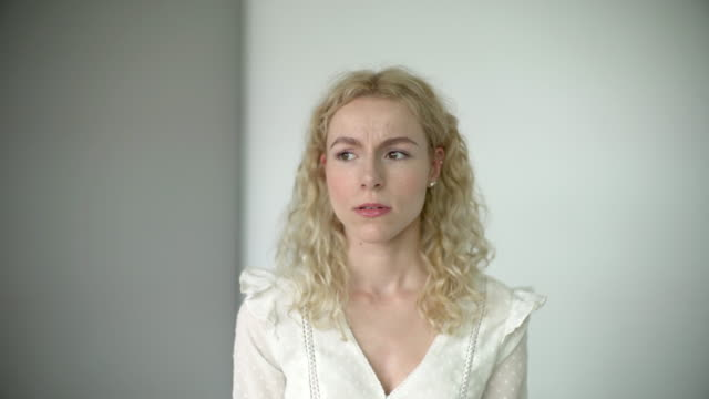 a daylight studio portrait of a young woman showing signs of sadness and emotion. - blonde hair stock videos & royalty-free footage