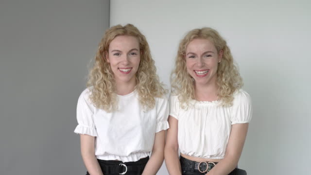 a daylight studio portrait of identical twin sisters. - identical twin stock videos & royalty-free footage