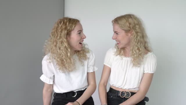 a daylight studio portrait of identical twin sisters. - twin stock videos & royalty-free footage