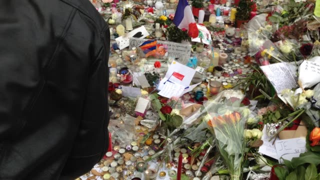 vidéos et rushes de days after the terrorist attacks in paris, members of the public continue to lay flowers and lit candles near the 'bataclan' theatre where 89 people... - rock moderne