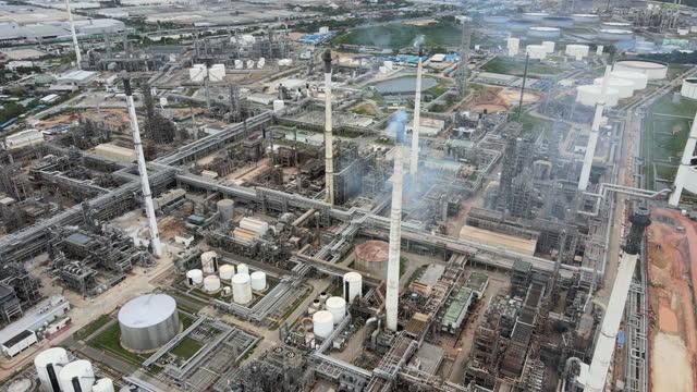 煙管の働きが付いているアジアの石油精製所および貯蔵タンクが付いている工業団地の空中の昼間4kのリアルタイム - 石油点の映像素材/bロール