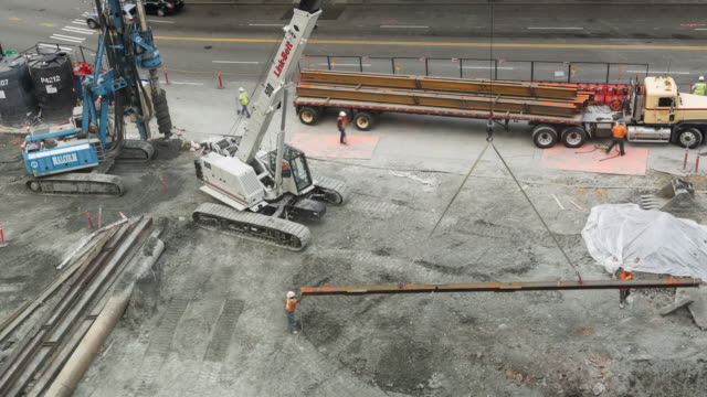 Daytime aerial time lapse of a crane offloading i-beams from a flatbed truck at a construction site with city traffic in the background