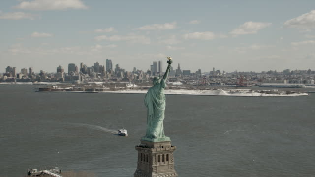 daytime, ariel view of the statue of liberty with brooklyn and manhattan in the background. - statue of liberty new york city stock videos & royalty-free footage