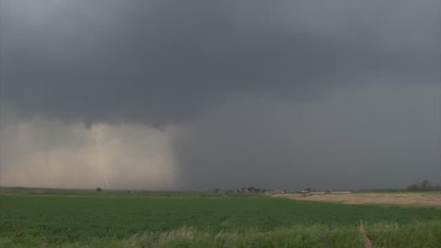 Daytime bright forked lightning under dark storm clouds across farm land