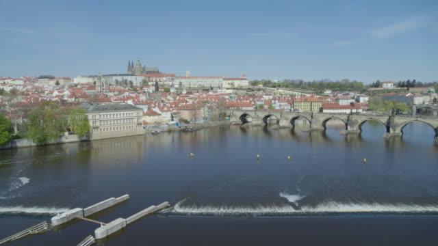 stockvideo's en b-roll-footage met daytime drone flight of a deserted charles bridge from the moldau river in prague, czech republic during the covid 19 shutdown/corona lockdown - redactioneel