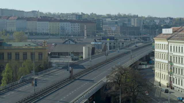 stockvideo's en b-roll-footage met daytime drone flight of a deserted street with crossroads and intersections in prague, czech republic during the covid 19 shutdown/corona lockdown - redactioneel
