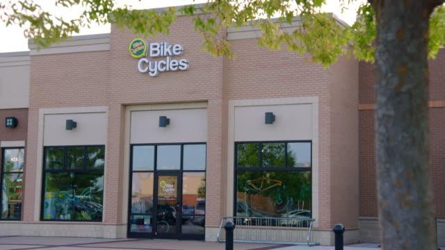 daytime exterior establishing shot of local bike shop - centro commerciale suburbano video stock e b–roll
