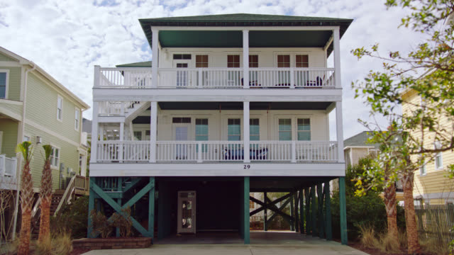 wide. daytime exterior of three-story beach house on intracoastal waterway between palm trees on cloudy day. - beach house stock videos & royalty-free footage