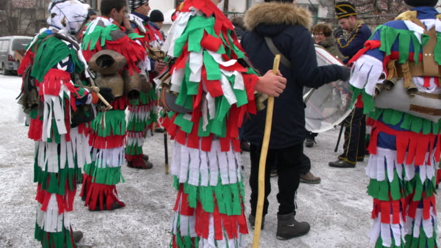 daytime kukeri parade with men and women dancing and jumping to the rhythm of bells and drums - bulgaria stock videos & royalty-free footage