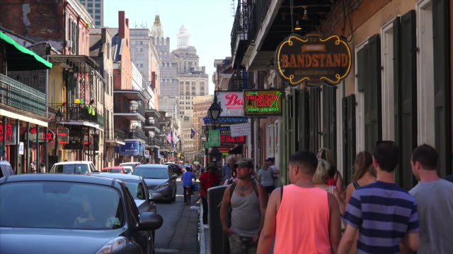 Daytime on Bourbon Street with traffic and tourists in French Quarter of New Orleans, Louisiana