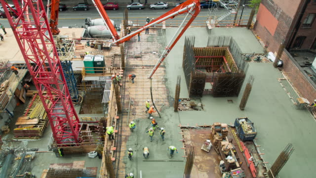 a daytime time lapse of a construction site in downtown seattle with a large machine pouring concrete while workers smooth it into a floor as a coordinated unit. - filiz stock videos & royalty-free footage