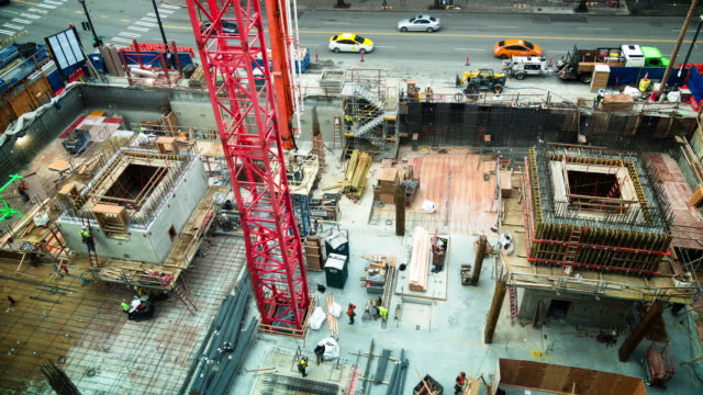 A daytime time lapse of a construction site in downtown Seattle with workers doing a wide assortment of tasks in the foreground and city traffic in the background.