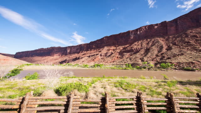 A daytime time lapse of a stretch of the Colorado River outside of Moad, Utah, with scrub in the foreground, cliffs in the background, and a blue sky with occasional high clouds.