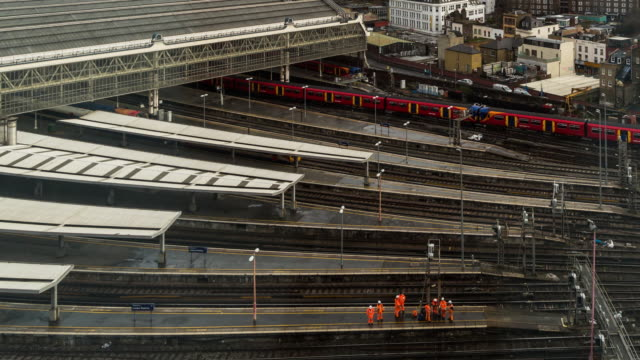 A daytime time lapse of a work crew at Waterloo Station (London, UK) performing a repair on a lamppost amid trains entering and leaving the station