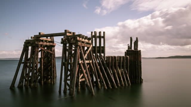 Daytime time lapse of an old ferry dock at Port Townsend, WA, with white clouds moving across a grey-blue sky