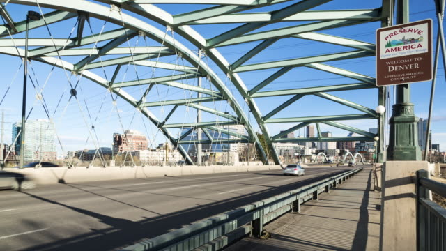 """A daytime time lapse of downtown Denver from the Speer Boulevard Platte River Bridge with a """"Welcome to Denver"""" sign clearly visible in the foreground"""