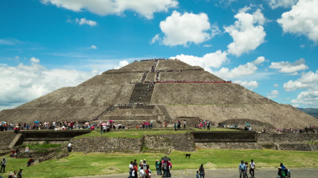 A daytime time lapse of the Pyramid of the Sun in Teotihuacan (outside of Mexico City, Mexico) with people streaming up and down the steps to the top and moving around the grounds.