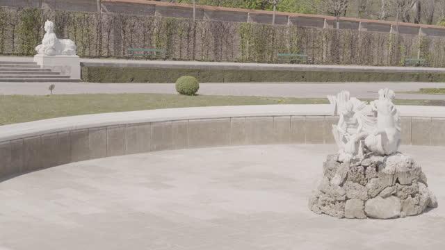 vidéos et rushes de daytime view of a deserted park of belvedere with a shut-off fountain in vienna, austria during the covid 19 shutdown/corona lockdown - palais du belvédère vienne