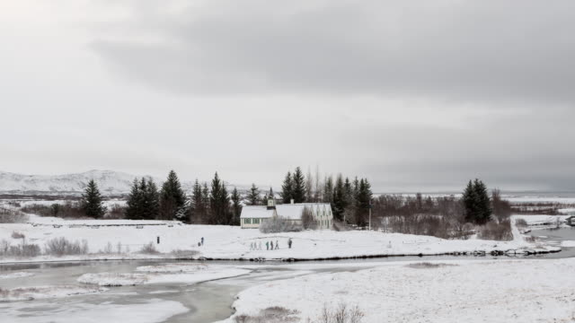 A daytime winter time lapse taken from the Þingvellir National Park in Iceland featuring tourists walking across a snow-covered field with a modern structure in the background (on the Golden Circle tour route)