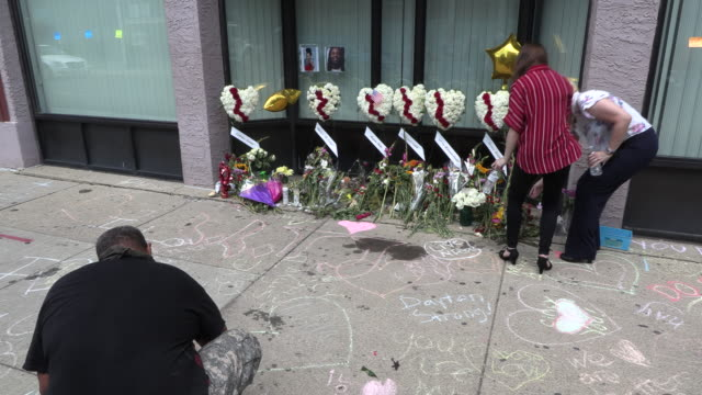 """dayton, ohio, usa: a man uses chalk to write, """"remember always,"""" at the site of sunday morning's mass shooting that left 9 dead, and 27 wounded,... - dayton ohio stock videos & royalty-free footage"""